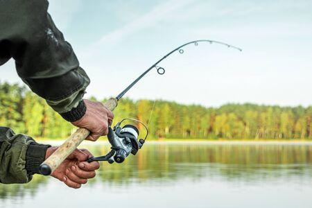 Les mains d'un homme tiennent une canne à pêche, un pêcheur attrape du poisson à l'aube.