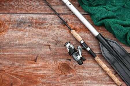 Paddle fishing rod and fishing net on a wooden background top view.