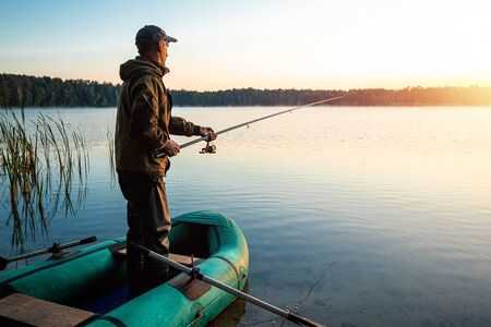 Male fisherman at dawn on the lake catches a fishing rod.