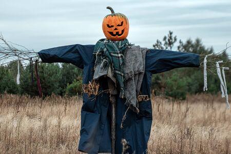 Un espantapájaros aterrador con una cabeza de calabaza de halloween en un campo en tiempo nublado. Fondo de Halloween, espacio de copia