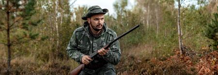 Hunter man in camouflage with a gun during the hunt in search of wild birds or game on the background of the autumn forest. Autumn hunting season. The concept of a hobby, killing. copy space.