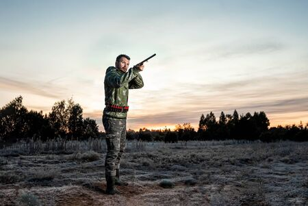 Hunter man in camouflage with a gun during the hunt in search of wild birds or game on a beautiful sunset. The concept of a hobby, killing. copy space.
