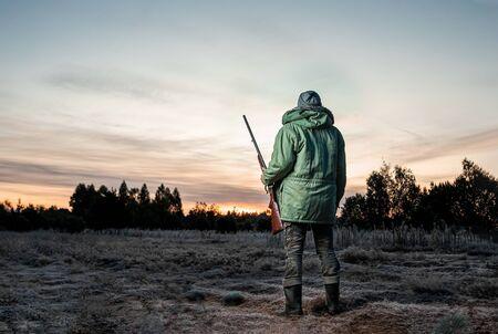 Homme chasseur en tenue de camouflage avec une arme à feu pendant la chasse à la recherche d'oiseaux sauvages ou de gibier sur un magnifique coucher de soleil. Le concept d'un passe-temps, tuer. espace de copie.