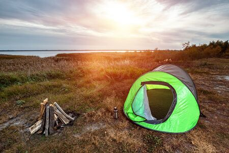 Camping tent green in the background of nature and lake. The concept of travel, tourism, camping 版權商用圖片