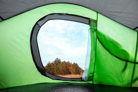 Camping view from the tent on the nature. The concept of travel, tourism, camping Фото со стока