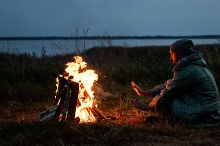 Camping man sitting by the fire at night against the sky. The concept of travel, tourism, camping