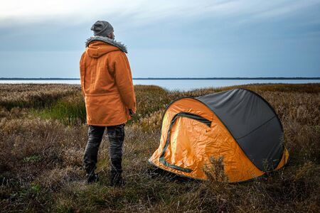 A bearded man near a camping tent in orange on the background of nature and the lake. The concept of travel, tourism, camping