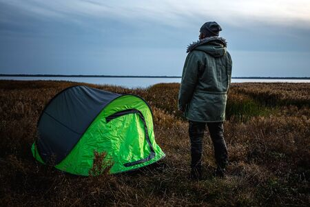 A bearded man near a camping tent in green on the background of nature and the lake. The concept of travel, tourism, camping