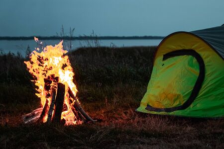 Camping man sits by the fire at night against the background of the starry sky. The concept of travel, tourism, camping