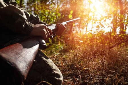 A hunter with a gun in his hands in hunting clothes in the autumn forest close-up. The hunting period, the fall season is open, the search for prey Stock Photo