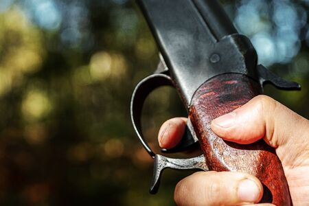 Finger on the trigger of a hunting rifle in the autumn forest close-up. The hunting period, the fall season is open, the search for prey Stock Photo