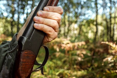 Finger on the trigger of a hunting rifle in the autumn forest close-up. The hunting period, the fall season is open, the search for prey Stok Fotoğraf