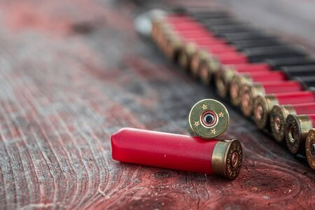 Hunting cartridges in patronage are lying on a wooden table close-up. The hunting period, the season is open