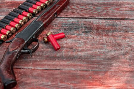 Shotgun and cartridges in patronage are lying on a wooden table top view. The hunting period, the season is open