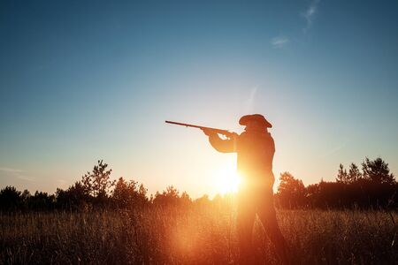 Silhouette of a hunter in a cowboy hat with a gun in his hands on a background of a beautiful sunset. The hunting period, the fall season is open, the search for prey
