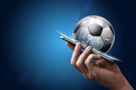 Smartphone en mano con un balón de fútbol 3D sobre un fondo azul. Apuestas, apuestas deportivas, casa de apuestas. Técnica mixta. Foto de archivo