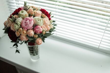 Wedding bouquet in a vase on the window. The concept of marriage, family relationships, wedding paraphernalia