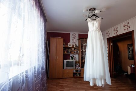 composition - a wedding dress on a gray blue wall with decor and accessories. The concept of marriage, family relationships, wedding paraphernalia