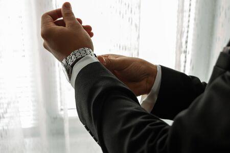 Hands of a businessman, close-up, buttons on a watch.