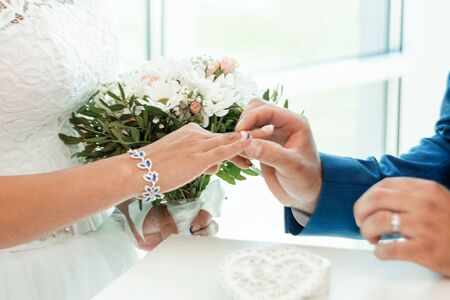 The bride and groom exchange rings, close-up. The concept of marriage, family relationships, wedding paraphernalia