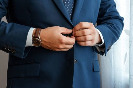 Hands of a businessman, close-up, buttons on a jacket. Concept of business style 免版税图像