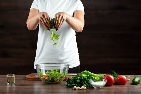 Woman cook cuts vegetables for salad preparation on a wooden background. Proper healthy eating