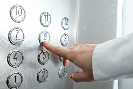 Main féminine, le doigt appuie sur le bouton de l'ascenseur. gravir les échelons de carrière