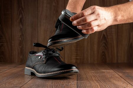 Men's hands clean black shoes on a wooden background. The concept of shoe shine, clothing care, services Stock Photo