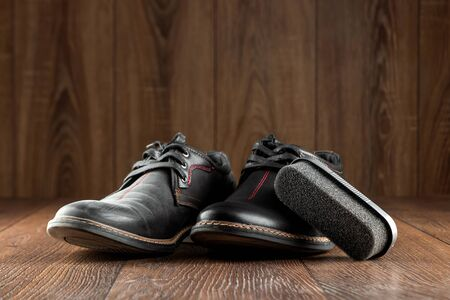 Black shoes one clean second dirty and brush on a wooden background. The concept of shoe shine, clothing care, services Stock Photo
