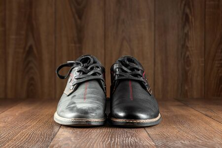 Black shoes one clean second dirty on a wooden background. The concept of shoe shine, clothing care, services