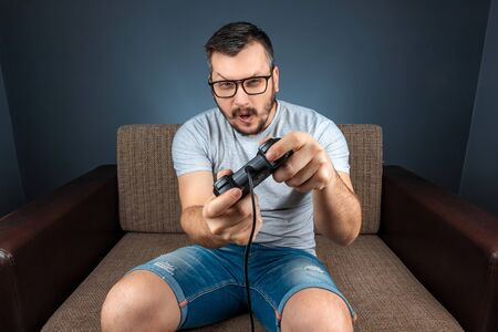 A man plays a video game console while sitting on a sofa. Day off, entertainment, leisure Stockfoto