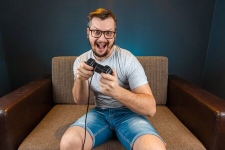 A man plays the console, video games react strongly and emotionally while sitting on the couch. Day off, entertainment, leisure