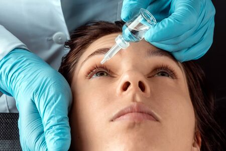 An ophthalmologist injects drops into the eyes of patients in an ophthalmic clinic. Health, vision, eye disease