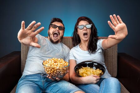 A man and a woman, a family watching a movie or a series in 3D glasses, a blue background. The concept of a cinema, films, emotions, surprise, leisure, streaming platforms
