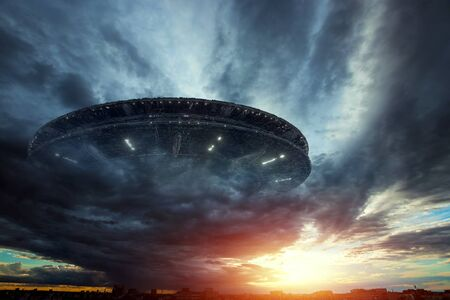 UFO, an alien plate soars in the sky, hovering motionless in the air. Unidentified flying object, alien invasion, extraterrestrial life, space travel, humanoid spaceship mixed medium Stok Fotoğraf