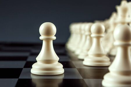 Close-up white pawn on a chessboard, chess, game. The concept of confrontation, career, promotion, startup Stock Photo