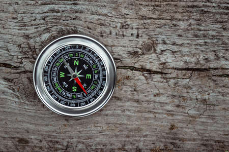 Silver compass on a wooden background top view. The concept of travel, leadership, help. Copy space
