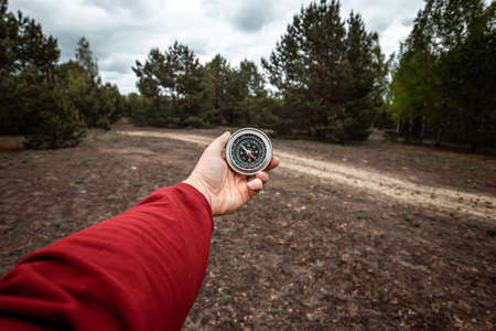 Compass in hand on a background of a landscape of mountains, Close-up. The concept of travel, hiking, vacation. Copy space