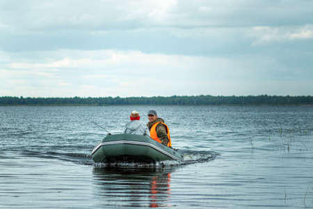 Father and son ride a motor boat on the lake. The concept of family, summer vacation, generation. Copy space