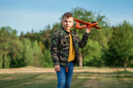 The boy launches a toy airplane against the backdrop of greenery. The concept of dreams, choice of profession, pilot, childhood. Copy space