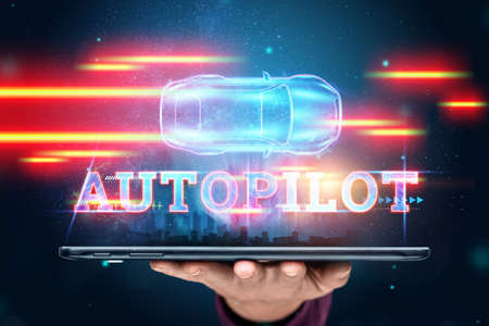 The hand of a man with a tablet and the inscription Autopilot, the car automatically detects the road and obstacles, scans the road. transport technologies. Hologram, copy space