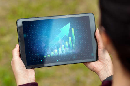 Close-up of a tablet in hands with the image of a graph with an upward arrow. New technologies. Copy space