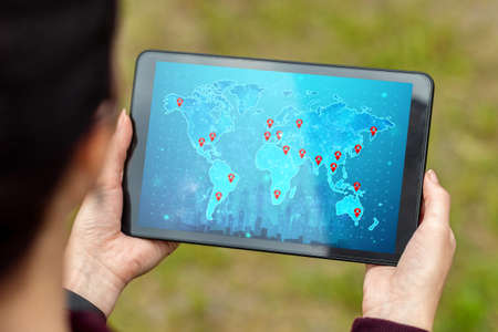 Close-up of a tablet in hands with a picture of a map of the whole world. New technologies. Copy space