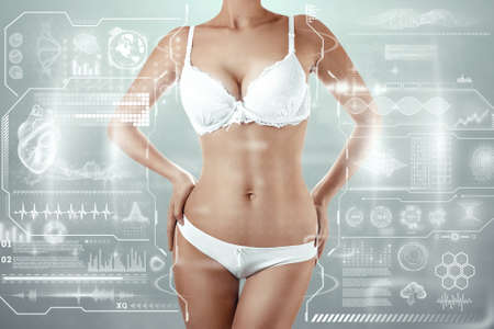 The body of a beautiful young girl on the background of a hologram with data. Spa treatments, new technologies, body care