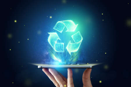 Sign Recycling hologram over the tablet on the hand. Eco recycling green symbol. The concept of clean land, garbage disposal