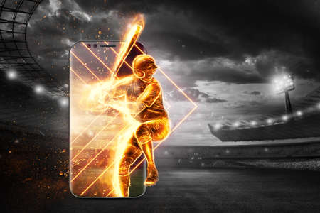 A silhouette, an image of a baseball player with a bat on fire crawls out of a smartphone, a hologram. Online sports concept, betting, American game