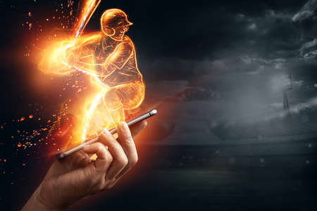 A silhouette, an image of a baseball player with a bat on fire crawls out of a smartphone, a hologram. Online sports concept, betting, American game 免版税图像