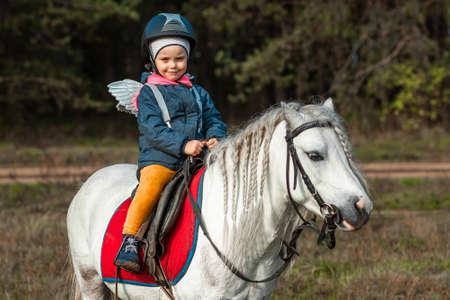 Little girl on a white pony on a background of nature. Jockey, hippodrome, horseback riding
