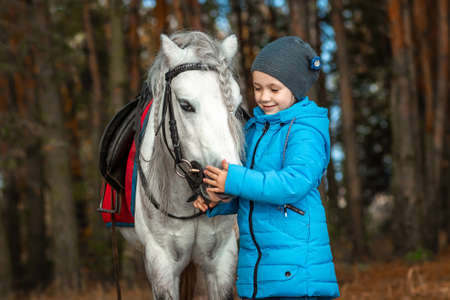 Little girl portrait, stands next to a white pony close-up on the background of nature. Jockey, epodrome, horseback riding. Stok Fotoğraf