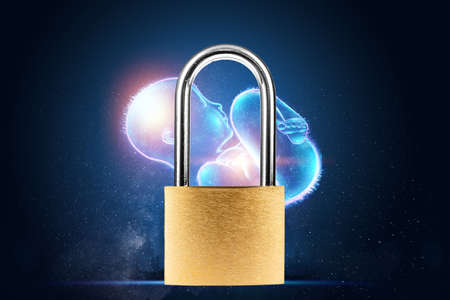Padlock on the background of a hologram of a child, baby. The concept of a ban on abortion, human rights, human life 版權商用圖片